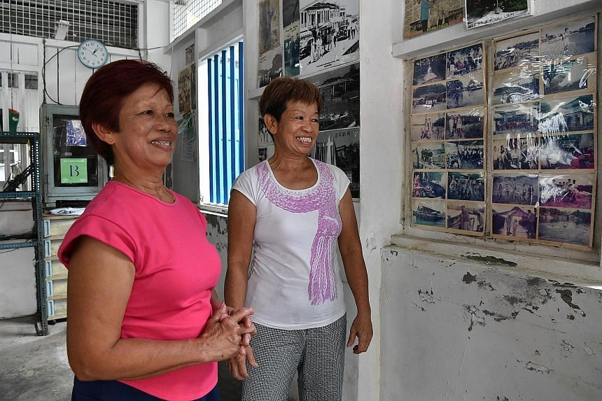 Sisters Goh Xin Eng (far left), 69, and Goh Guat Lai, 63, looking at old photos pasted on the wall of the first storey of the Pulau Ubin building (above) where they run the Sin Lam Huat eatery that was first opened and operated by their parents. ST P