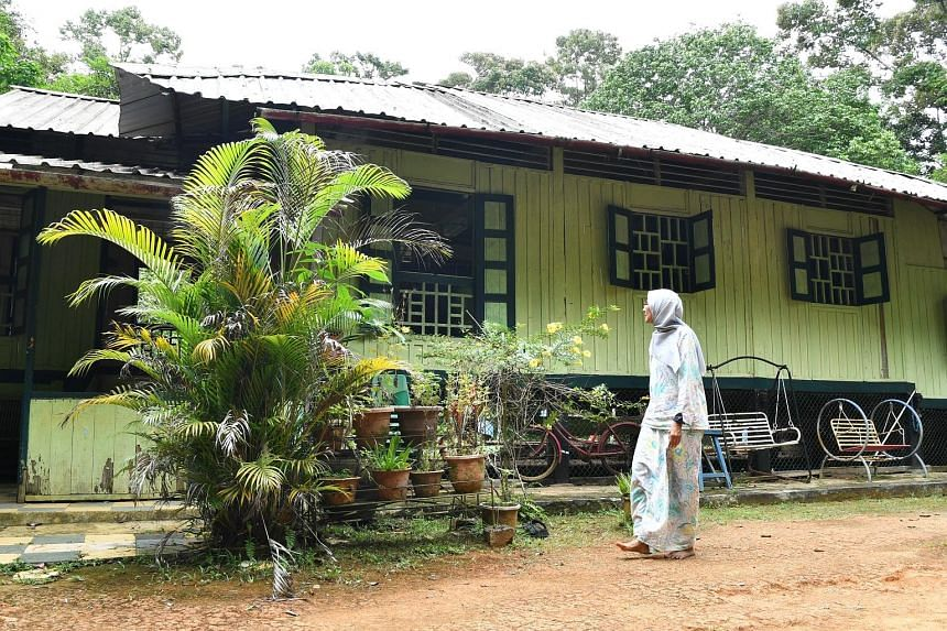Madam Kamariah Abdullah outside her house on Pulau Ubin. She said she is grateful for the help she is getting to repair the ageing structure she grew up in, noting that it often takes a battering from strong winds and rain, as well as other forces of