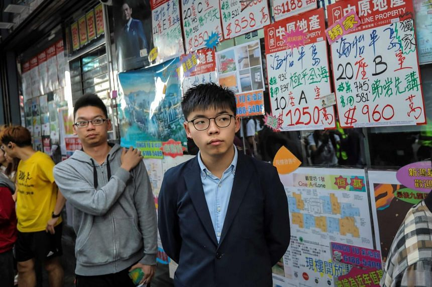 Pro-democracy activist Joshua Wong (right), who was disqualified from running in the elections, queuing up to cast his vote in the South Horizons district of Hong Kong.