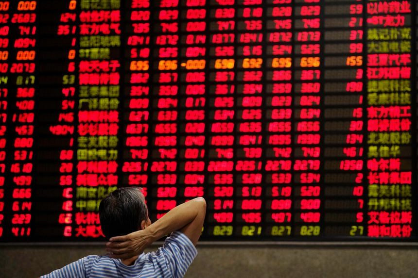 An investor looks at an electronic board showing stock information at a brokerage house in Shanghai, China.
