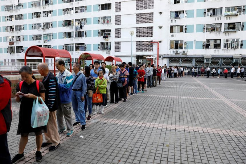 People queue outside a polling station during district council local elections in Hong Kong, on Nov 24, 2019.