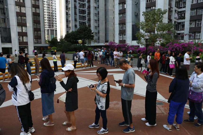 Voters queue to vote at a polling station during district council local elections in Hong Kong on Nov 24, 2019.
