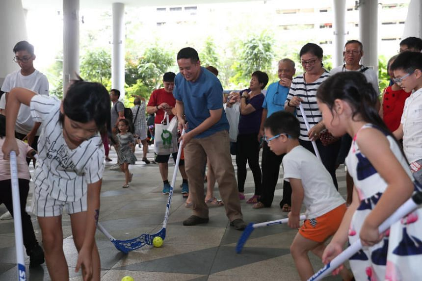 Senior Parliamentary Secretary for Health and Home Affairs Amrin Amin playing floorball with children at the Family Health and Wellness Carnival at Kampung Admiralty on Nov 24, 2019.