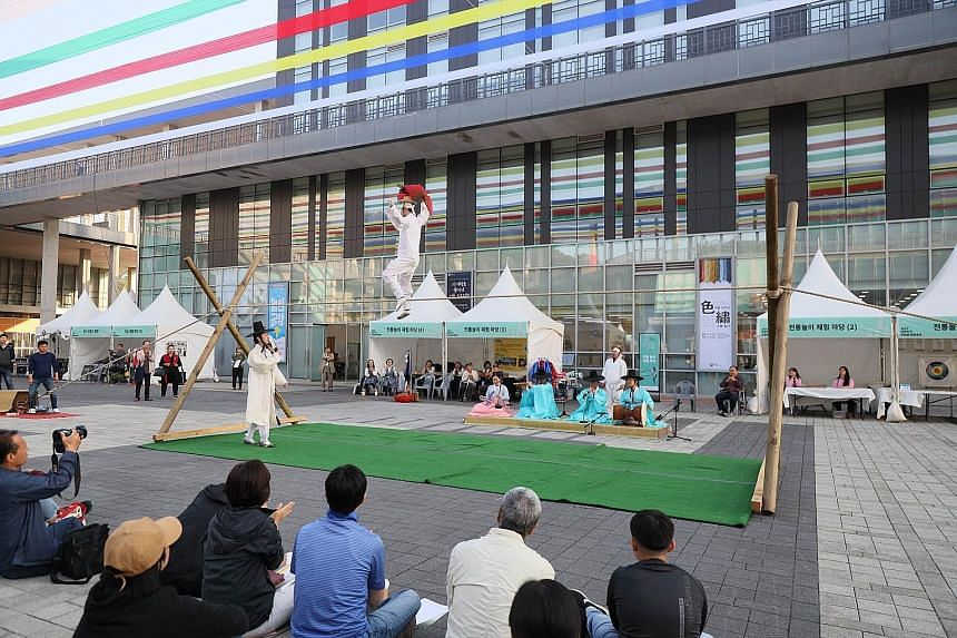 """The traditional Korean art of tightrope walking, accompanied by music and witty dialogue between the tightrope walker and a """"clown"""" on the ground, being performed in South Korea last month. PHOTO: NATIONAL INTANGIBLE HERITAGE CENTRE"""