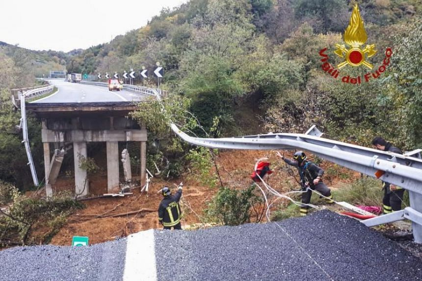 A photo taken and released on Nov 24, 2019 by the Italian Department of Firefighter, shows rescuers intervening after a viaduct section of the A6 highway between Turin and Savona collapsed following a landslide near Savona.