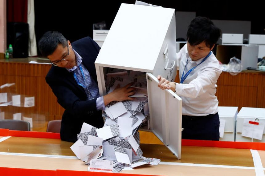 Officials open a ballot box at the polling station in the South Horizons West district as voting officially closes in Hong Kong on Nov 24, 2019.