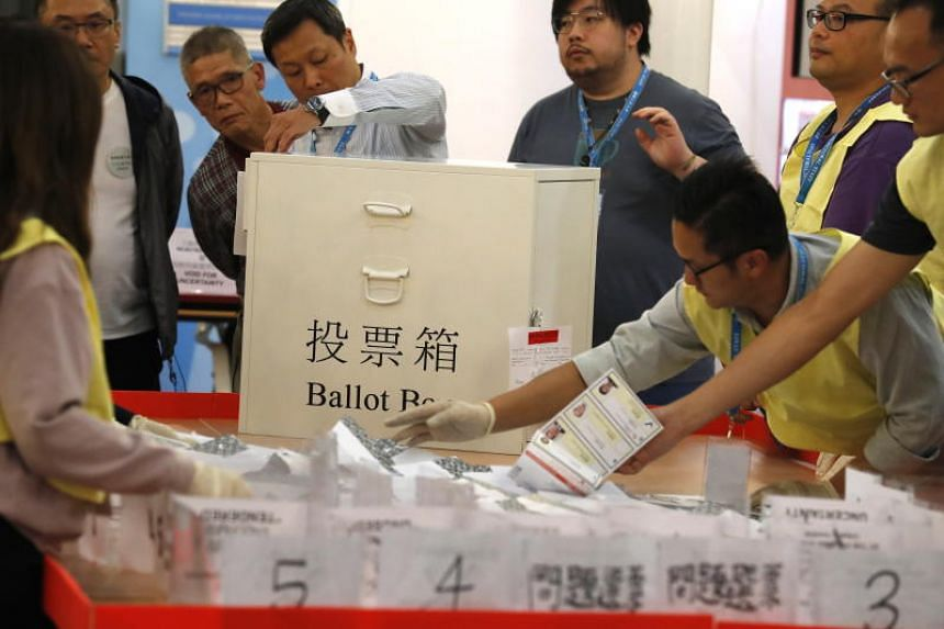 Officials count ballots at a polling station as voting officially closes in Hong Kong on Nov 24, 2019.
