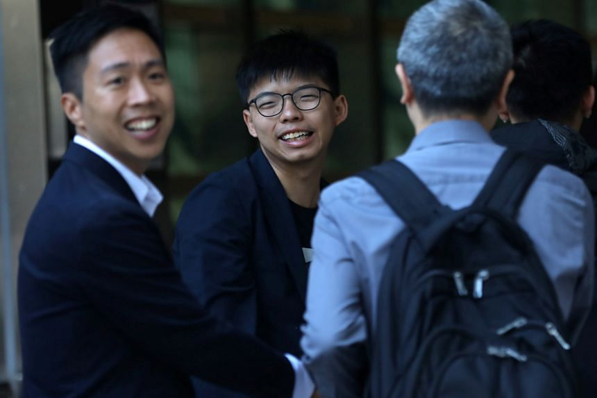 Candidate Kelvin Lam (left) and activist Joshua Wong greeting supporters outside South Horizons station, in Hong Kong, on Nov 25, 2019, the morning after Mr Lam won in district council elections.