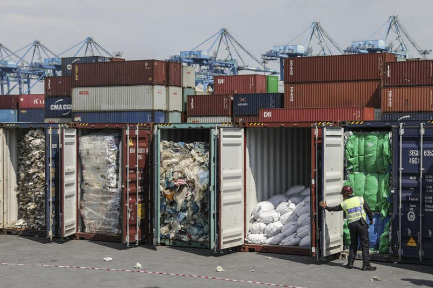 An auxiliary police officer inspects plastic waste inside cargo containers in Port Klang, Selangor, Malaysia, on May 28, 2019.