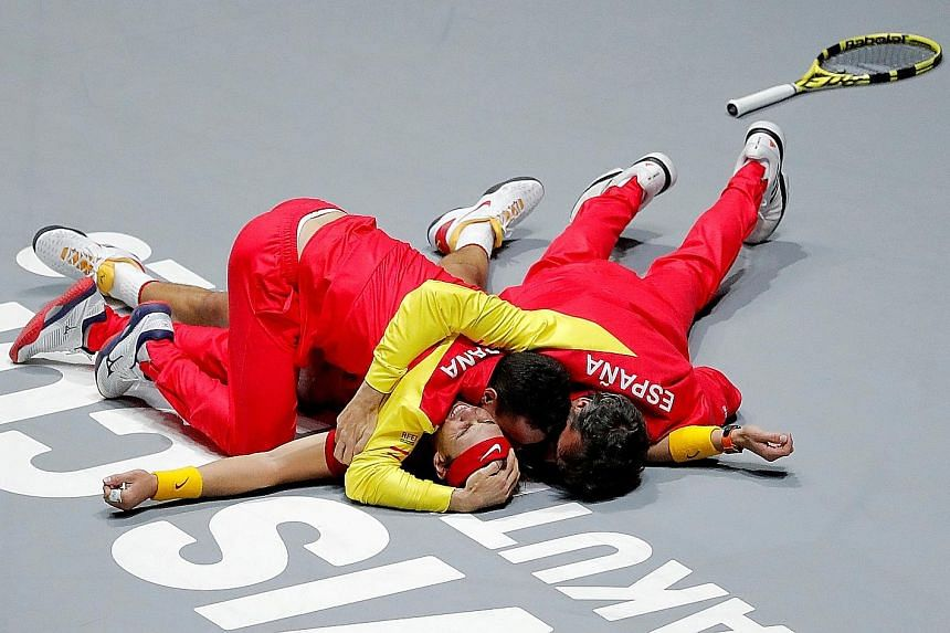 Rafael Nadal's teammates piling on him to celebrate Spain's winning point in the Davis Cup, after he beat Canada's Denis Shapovalov in Madrid on Sunday. It is the country's sixth title. PHOTO: REUTERS