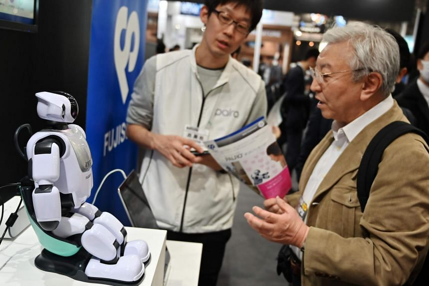 Visitors looking at Palro, a robot developed by Fujisoft, at the Artificial Intelligence expo in Tokyo on April 5, 2019.