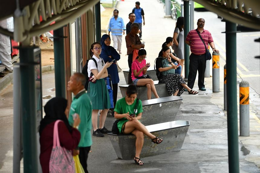 People waiting at the bus stop outside Haig Road Market & Food Center on Sept 25, 2019.