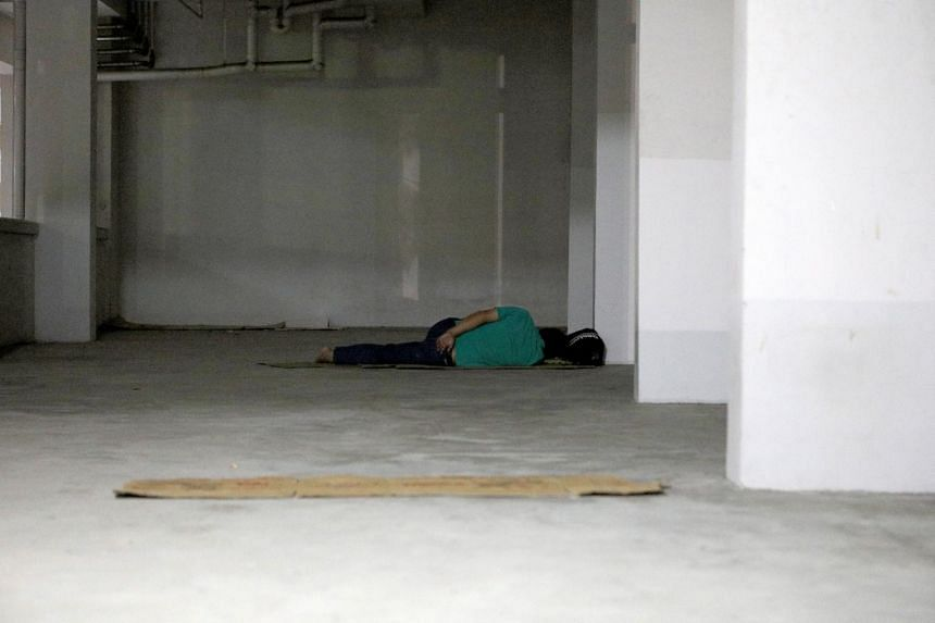 A homeless man sleeping at a void deck.