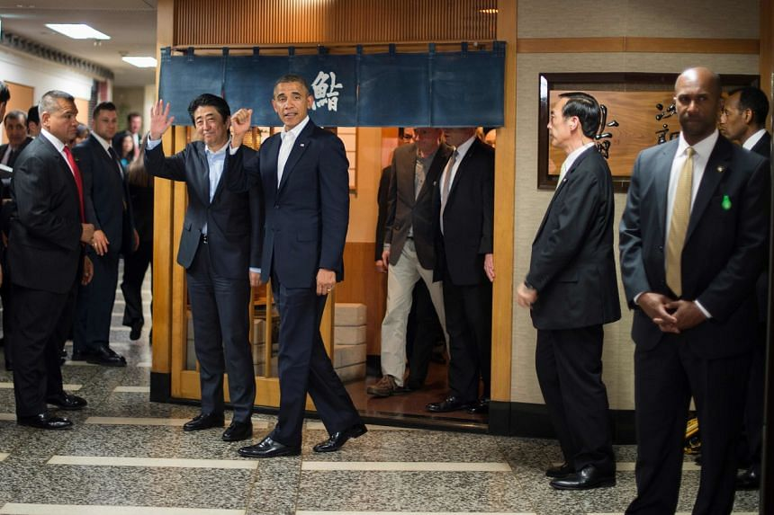 In a photo taken on April 23, 2014, then US President Barack Obama (centre) and Japan's PM Shinzo Abe (second from left) depart after a private dinner at the Sukiyabashi Jiro restaurant in Tokyo.