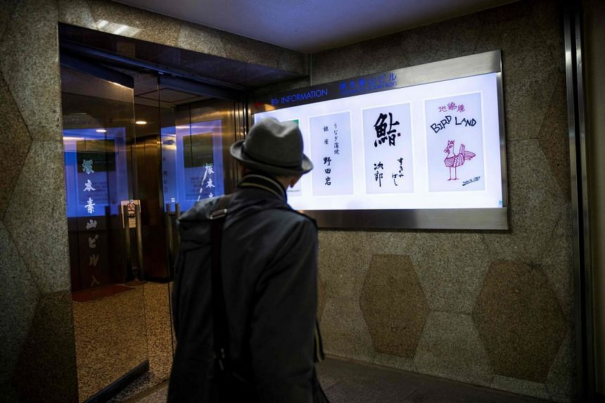 A man walks past the board displaying the logo of Sukiyabashi Jiro restaurant (second from right) in Tokyo, on Nov 26, 2019.