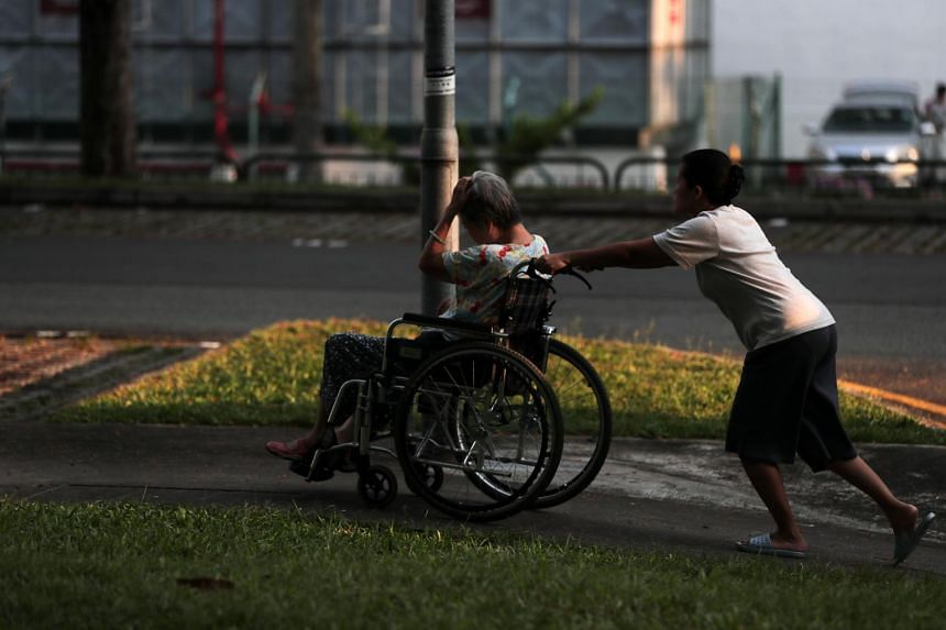 A helper pushes an elderly woman in a wheelchair.