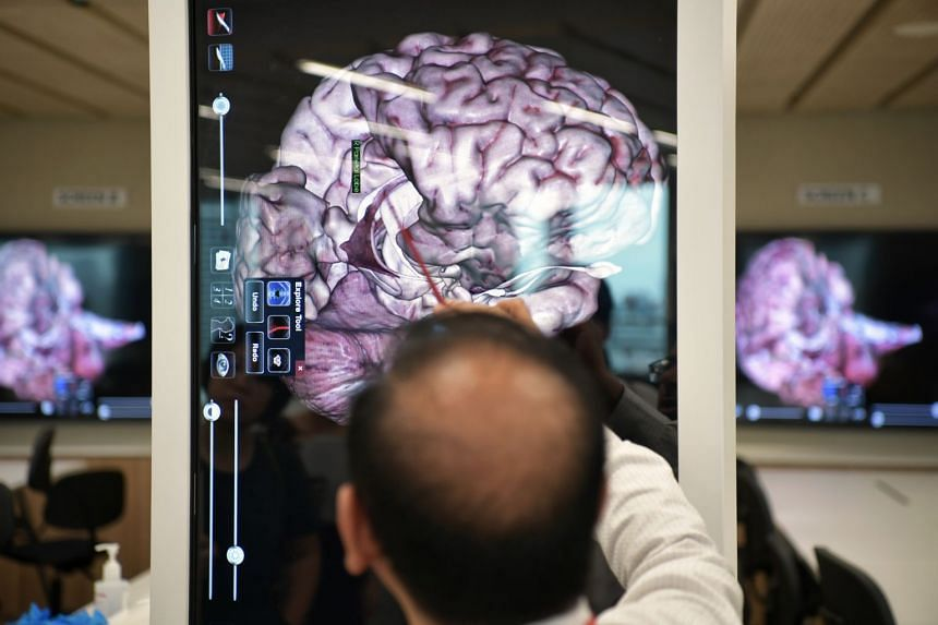 Dr Ranganath, Senior Lecturer in Anatomy at the Lee Kong Chian School of Medicine, demonstrates the use of the Anatomage, a virtual dissection tablet during the launch of Singapore's first brain bank on Nov 27, 2019.