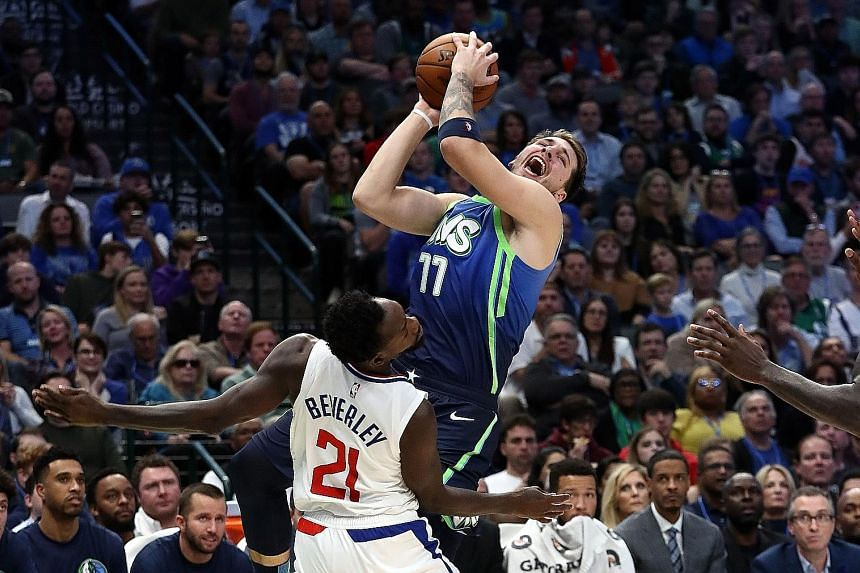 Luka Doncic of the Dallas Mavericks is fouled by the Los Angeles Clippers' Patrick Beverley during their NBA game at the American Airlines Centre on Tuesday night. The Clippers won 114-99 to improve to 13-5 and extended their winning streak to six ga