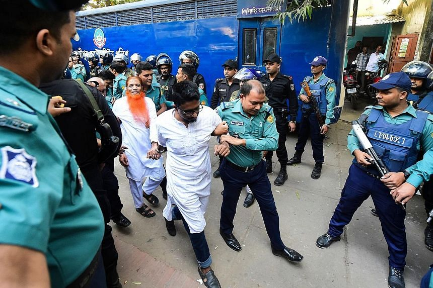 Police escorting members of an Islamist militant group, who were accused of plotting the 2016 Holey Artisan cafe attack, to a courtroom for their trial and sentencing in Dhaka yesterday. PHOTO: AGENCE FRANCE-PRESSE
