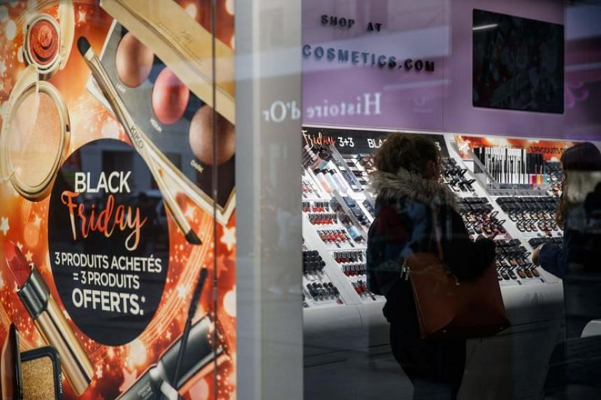 Shoppers look at items in a cosmetics shop ahead of Black Friday sales in Caen, France, on Nov 27, 2019.