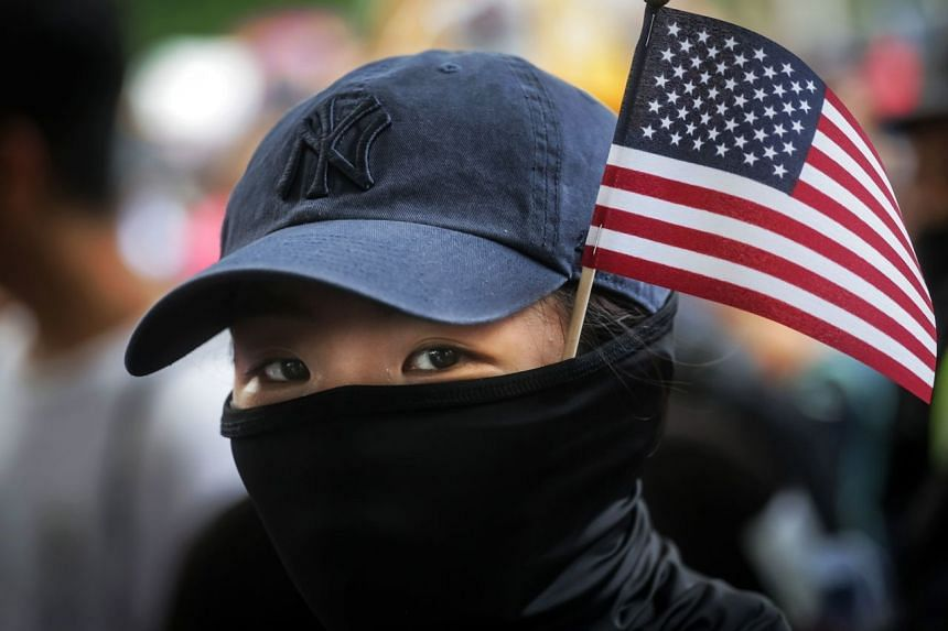 In a photo taken on Sept 8, 2019, a protester with a US national flag sticking out from her mask takes part in a march from Chater Garden to the US Consulate in Hong Kong.