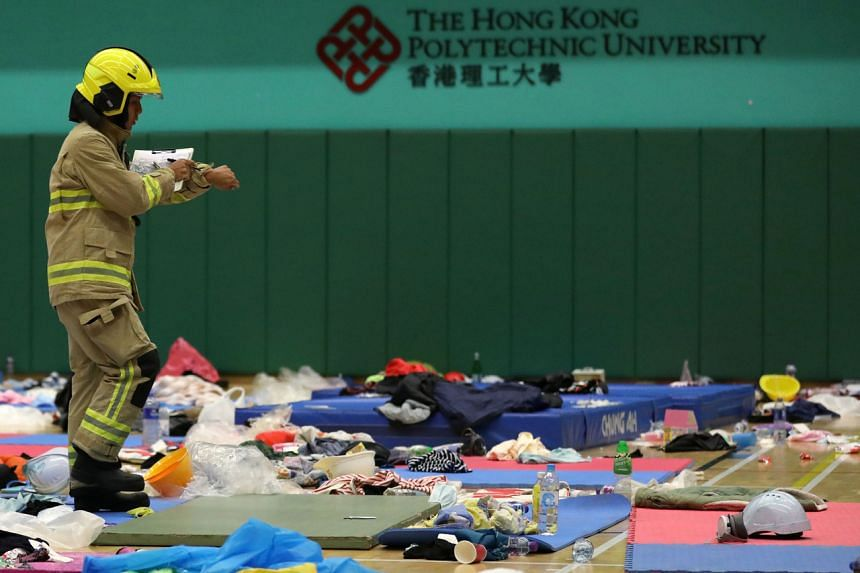 A member of a safety team established by Hong Kong authorities sorts through items left by protesters at Hong Kong Polytechnic University on Nov 28, 2019.