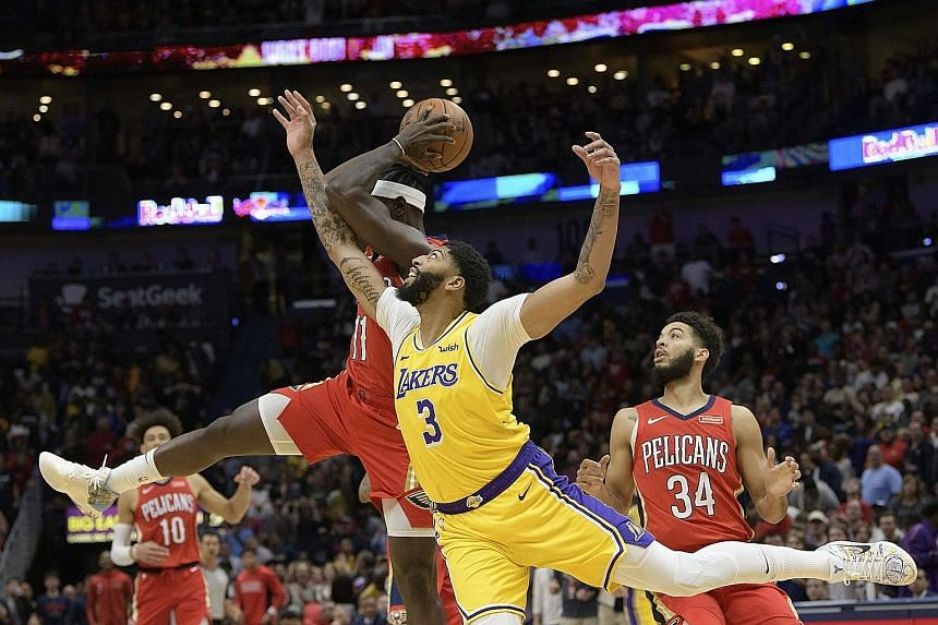 LA Lakers forward Anthony Davis battling for the ball with New Orleans' Jrue Holiday. It was Davis' first game against his old team, the Pelicans, following his summer move.