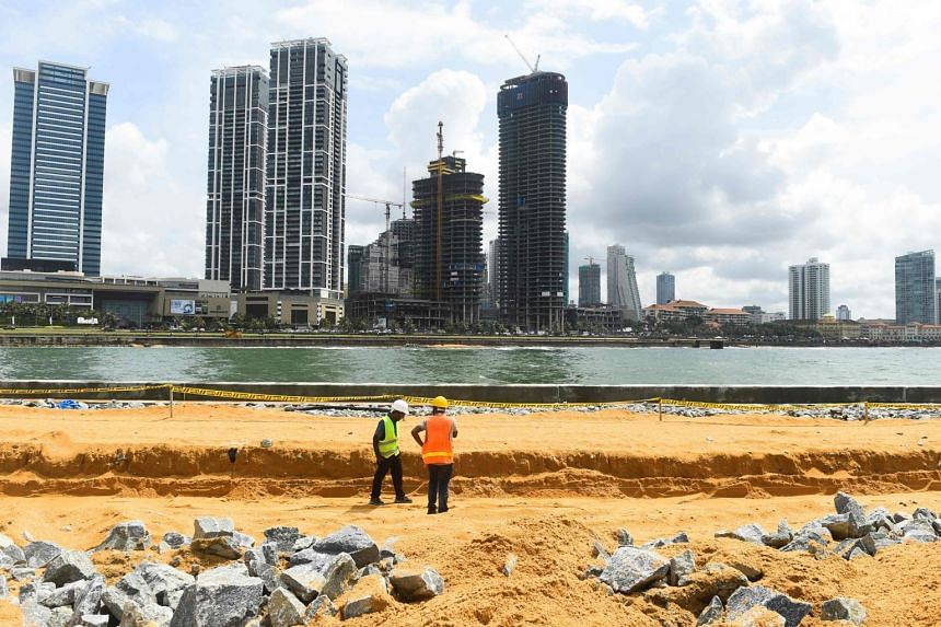 In a picture taken on Nov 8, 2019, labourers work at the construction site on reclaimed land as part of the Chinese-funded project for Port City in Colombo.