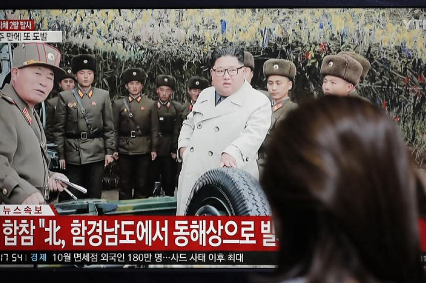 A woman watches a news programme reporting North Korea firing unidentified projectiles with a file image of North Korean leader Kim Jong Un, in Seoul on Nov 28, 2019.