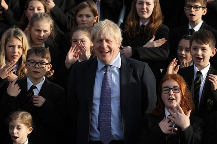 Britain's Prime Minister and Conservative Party leader, Boris Johnson (centre), joins the Chulmleigh College school choir while campaigning for the general election in Devon, southwest England, on Nov 28, 2019.