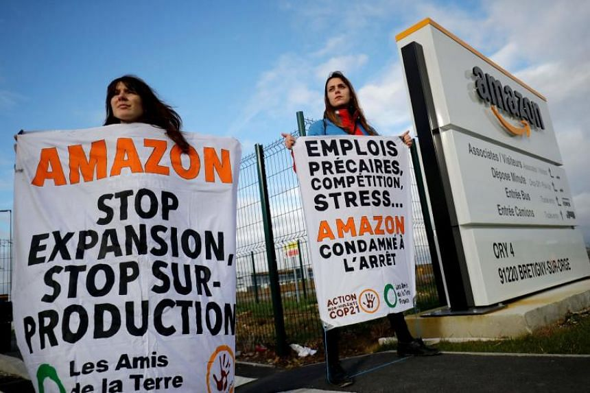 Environmental activists block an Amazon centre in Bretigny-sur-Orge, France on Nov 28, 2019, to protest against the company's labour policies and impact on climate change.
