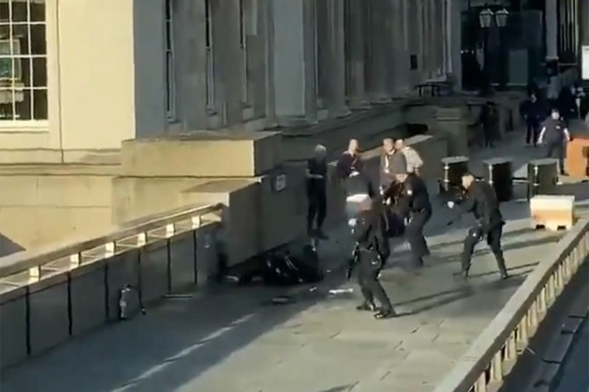 Videos on Twitter show police officers backing away from the suspect lying on the pavement.