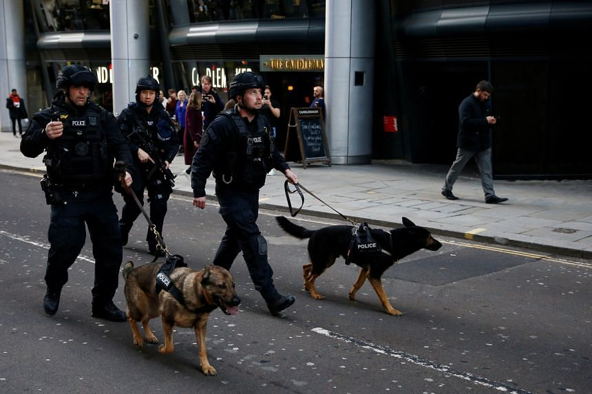 Police officers with sniffer dogs are seen near the site of an incident at London Bridge in London on Nov 29, 2019.