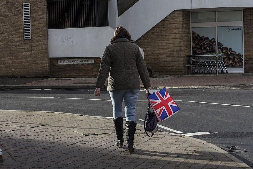 """A woman with a reusable bag with a Union Jack design. The 10 firms making up most of Britain's grocery retailers sold over 1.5 billion """"bags for life"""" this year."""