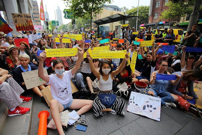 """Student activists from the School Strike for Climate Australia holding a """"solidarity sit-down"""" outside the ruling Liberal Party's office in Sydney, Australia, yesterday. PHOTO: EPA-EFE"""