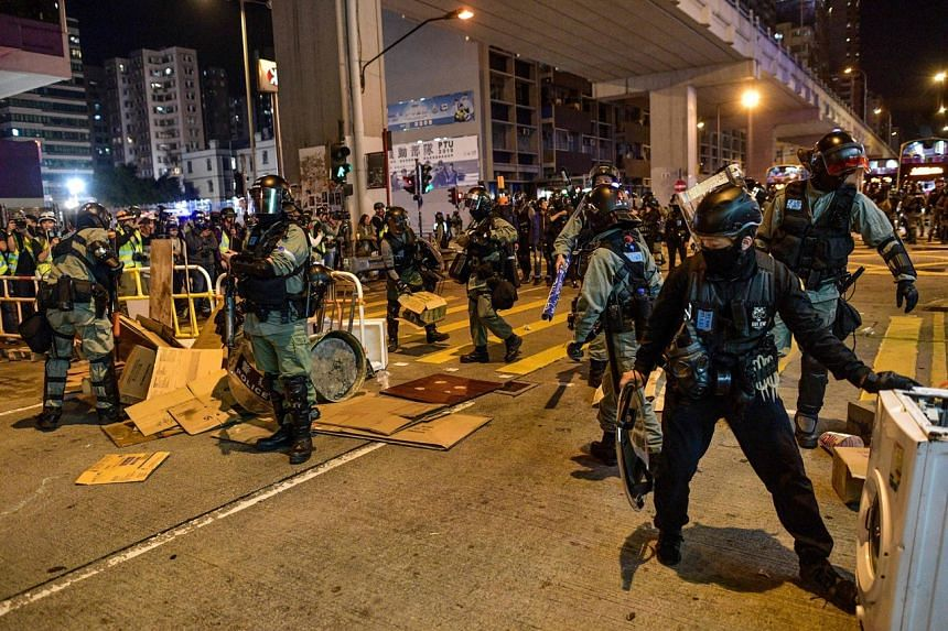 Police clear a barricade set up by protesters outside a police station in Hong Kong's Mongkok area on Nov 30, 2019.