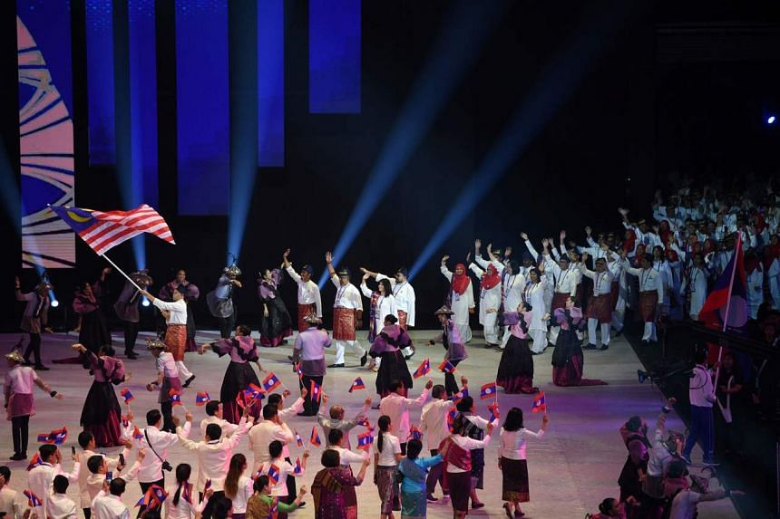 Athletes and officials from Malaysia (top) and Laos (bottom) march during the opening ceremony of the SEA Games at the Philippine Arena in Bocaue on Nov 30, 2019.