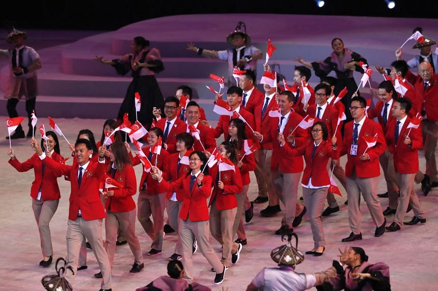 Athletes and officials from Singapore march during the opening ceremony of the SEA Games at the Philippine Arena in Bocaue on Nov 30, 2019.