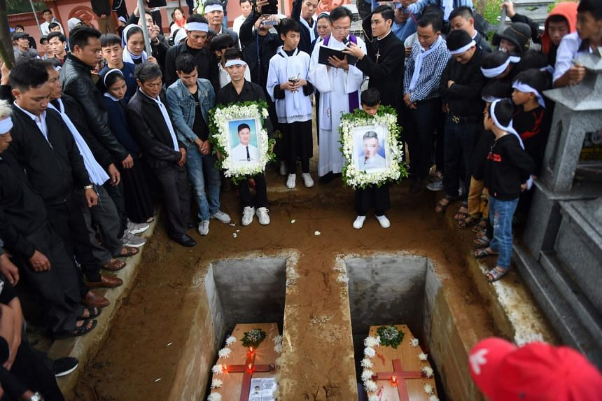 A priest officiates final rites during burial of coffins bearing the remains of Nguyen Van Hung (left) and Hoang Van Tiep at a cemetery in Dien Chau district, Nghe An province, on Nov 28, 2019.