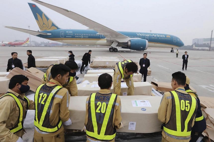 Airport personnel line up a row of coffins on the tarmac of the Noi Bai airport in Hanoi, Vietnam, on Nov 30, 2019.