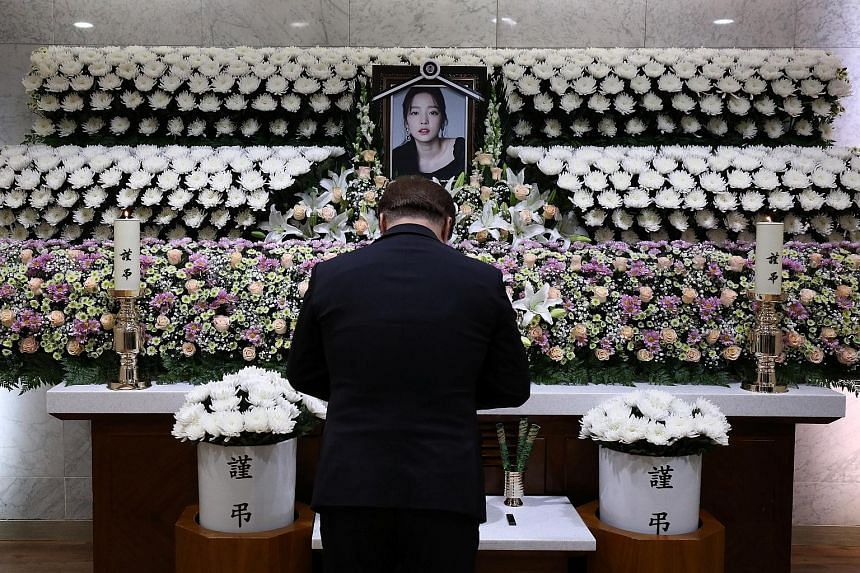 A man paying his respects at a memorial altar for another K-pop star, Goo Hara. The 28-year-old committed suicide six weeks after Sulli's death.