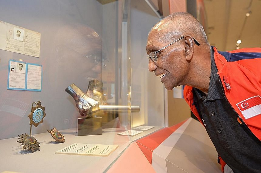 Singapore sprint legend C. Kunalan looking at his 100m silver medal (above) from the 1966 Bangkok Asian Games in the Singapore Sports Museum.