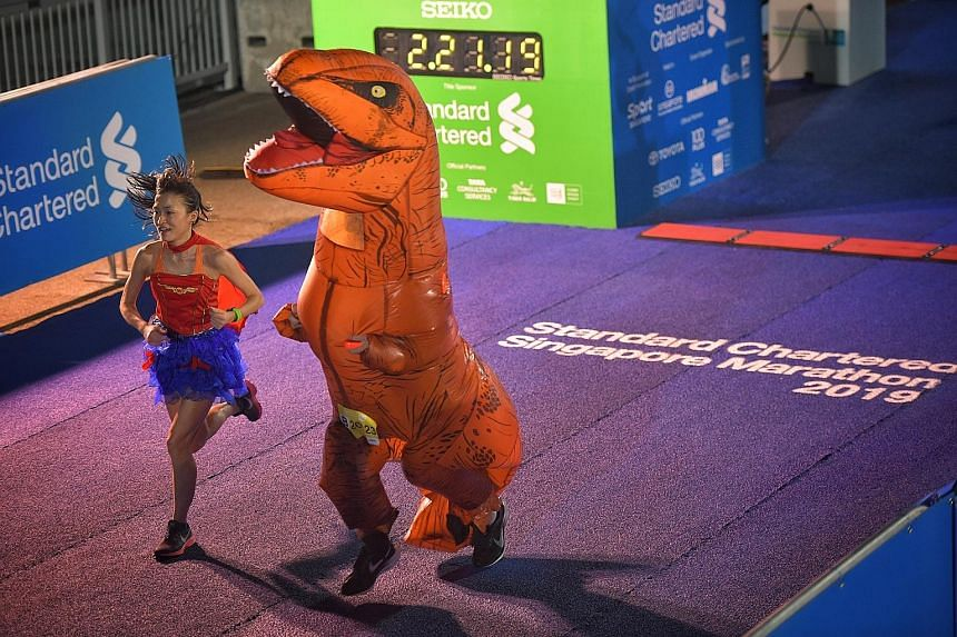 A runner dressed in non-traditional gear getting a second wind towards the finish line as she breezes past a character from Jurassic Park.