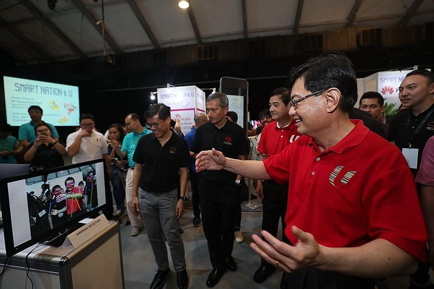 Deputy Prime Minister Heng Swee Keat visiting a booth at the Smart Nation & U event yesterday, where he urged Singaporeans to progress together technologically. The event had activities such as a digital clinic where seniors could learn how to make their