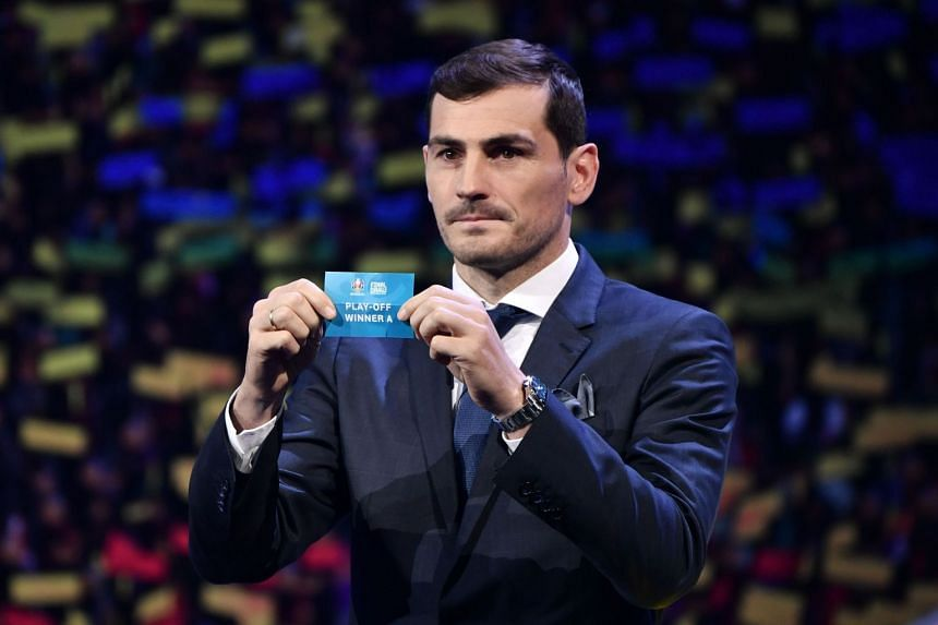 Spanish footballer Iker Casillas holds up a slip of paper after drawing the Play-Off Winner A from the pot.