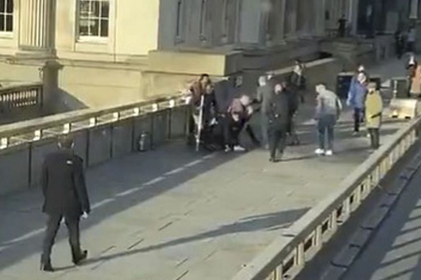 A video grab shows the attacker surrounded by members of the public before armed police arrive.