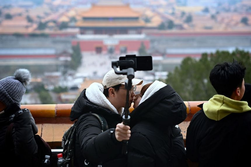 A couple kiss as they pose for a selfie at a park in Beijing, on Nov 29, 2019. An app is working with more than 90 Aids-prevention organisations to carry out anti-Aids advertising and intervention, and to make HIV testing just a tap away for app user