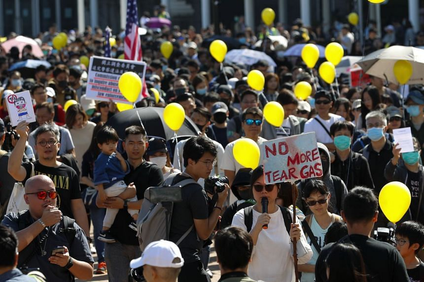 """People holding balloons march as they take part in a """"No Tear Gas"""" rally in Hong Kong, on Dec 1, 2019."""