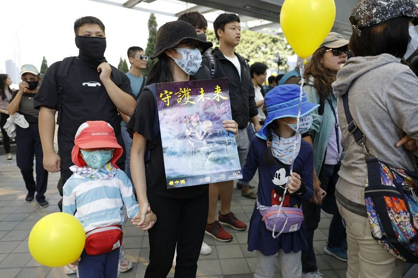 """A masked woman and children hold balloons and a placard which reads """"Guard the Future"""" during a """"No Tear Gas"""" rally march in Hong Kong, on Dec 1, 2019."""