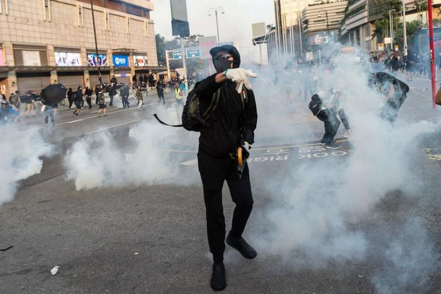 Pro-democracy protesters reacting to tear gas fired by police during a march, on Dec 1, 2019.